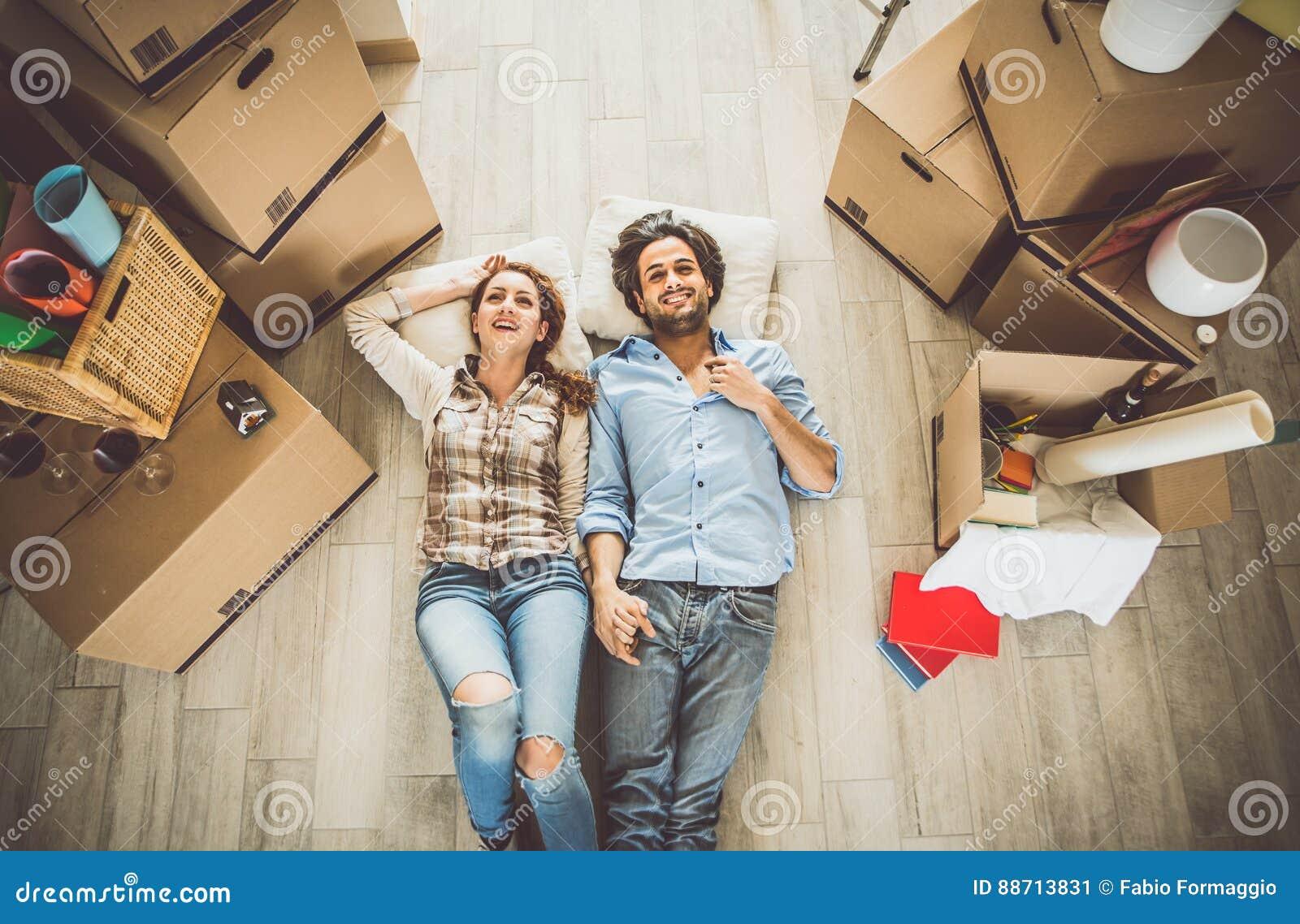 Pares jovenes que se trasladan adentro al nuevo apartamento