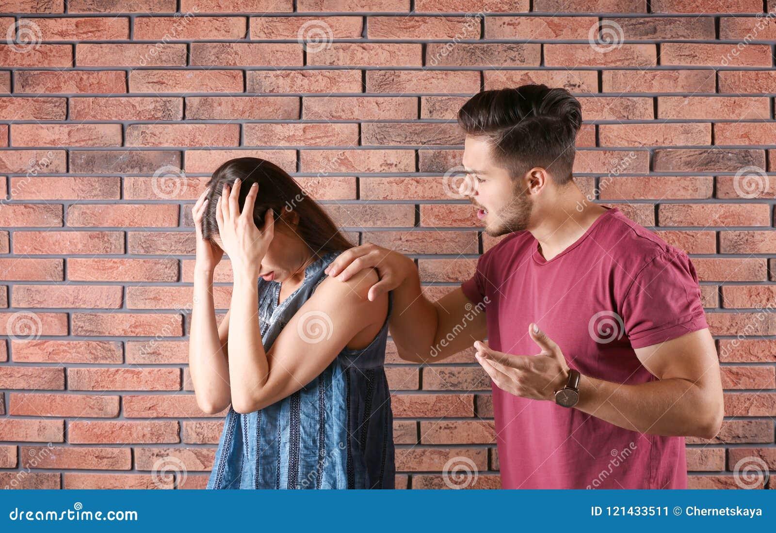 Pares jovenes que tienen discusión cerca de la pared de ladrillo