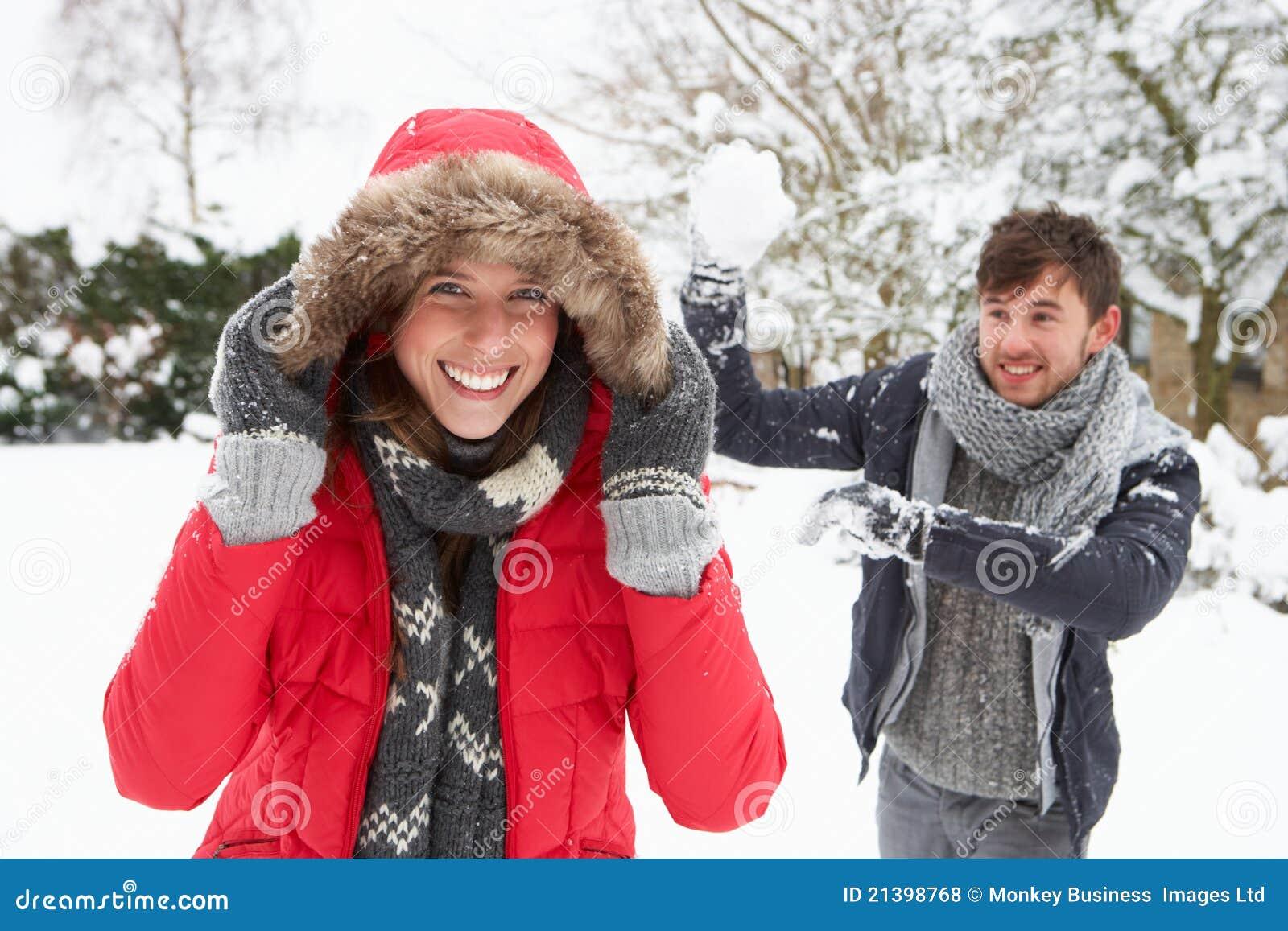 Pares jovenes que tienen lucha de la bola de nieve