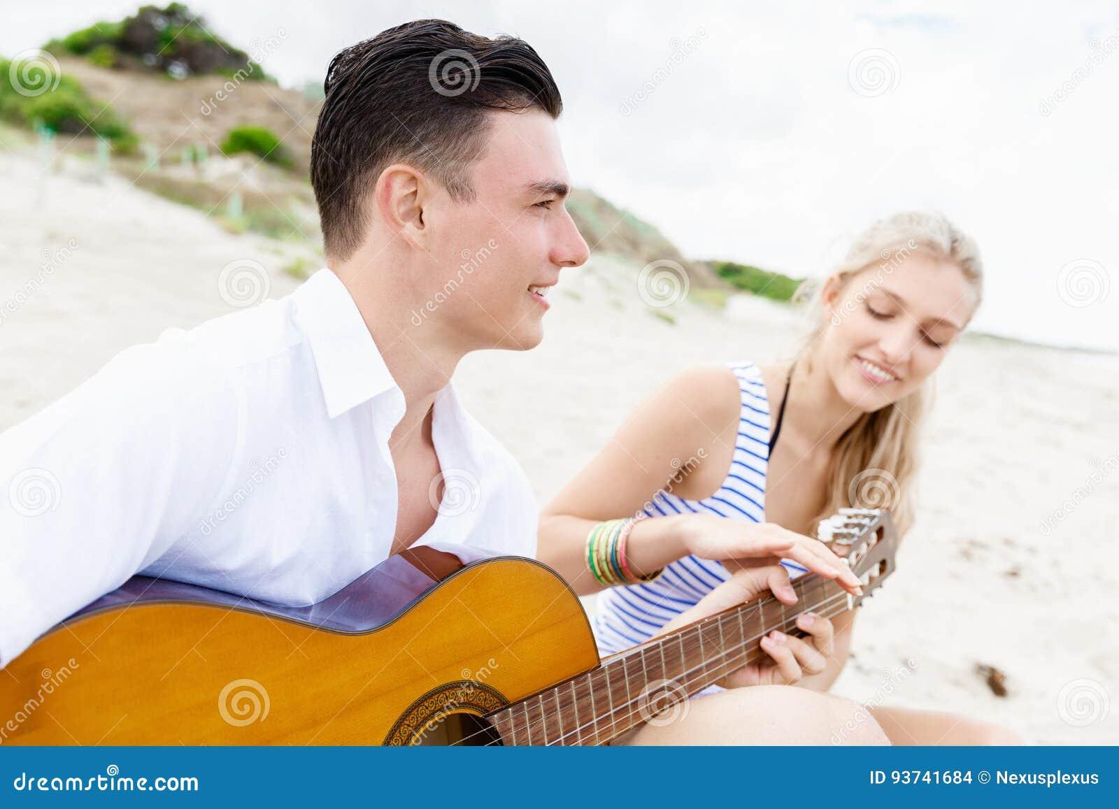 Pares jovenes que tocan la guitarra en la playa en amor
