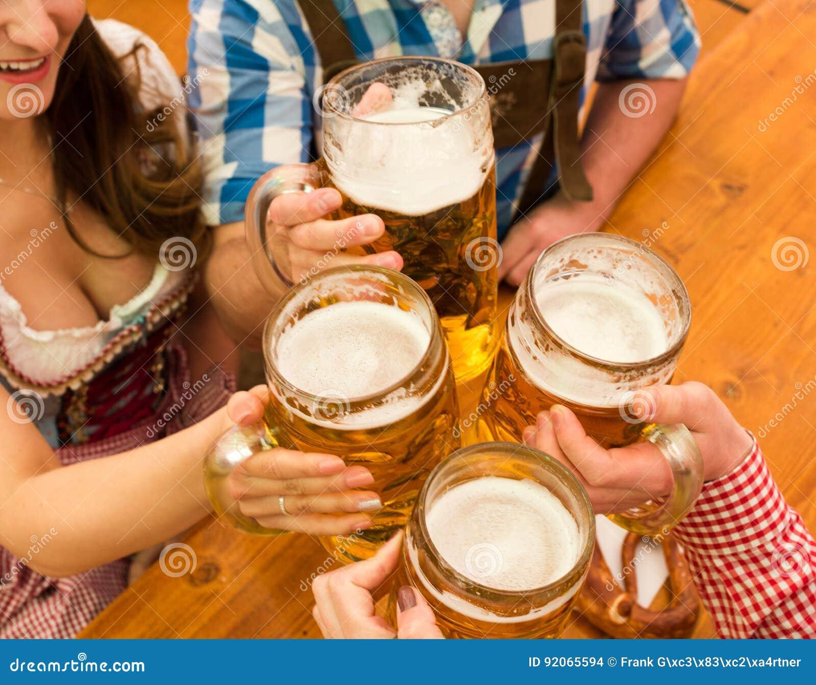 Pares jovenes que tuestan en tienda de la cerveza de Oktoberfest