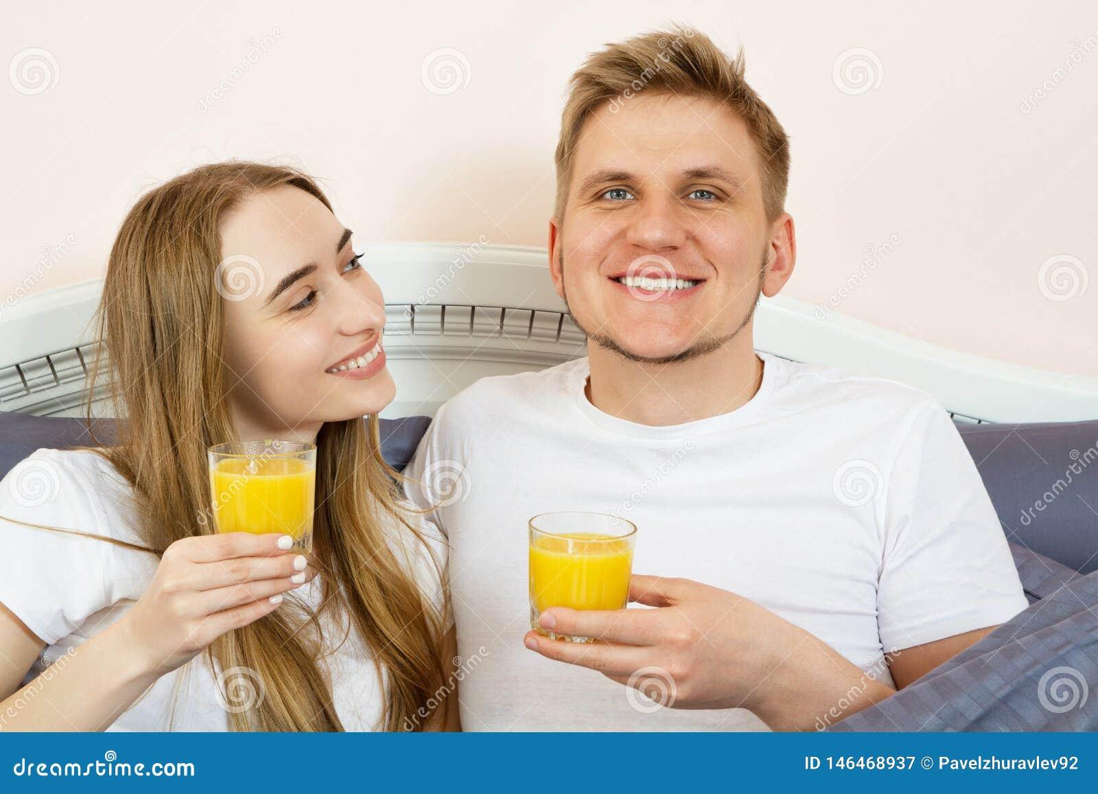 Pares jovenes relajados felices con el zumo de naranja en cama en casa Pares románticos que beben el zumo de naranja que miente e