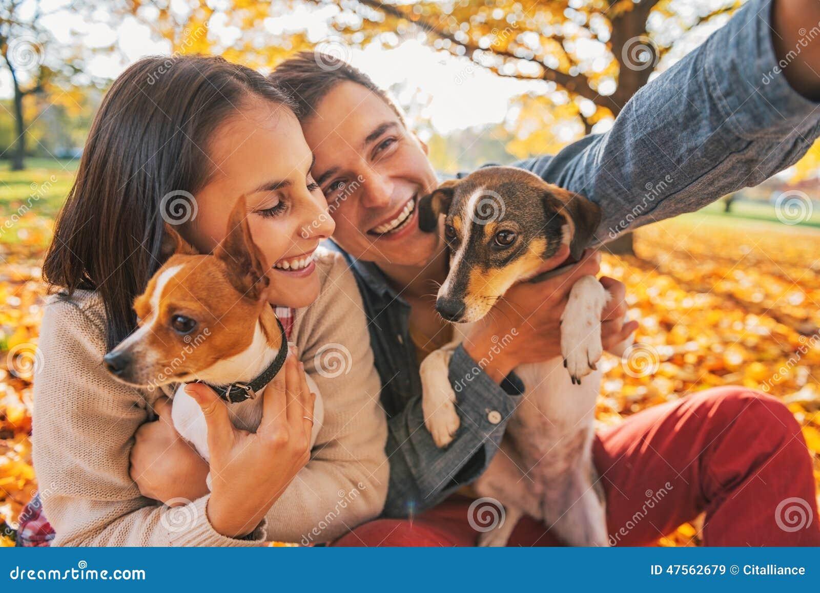 Pares jovenes sonrientes con los perros al aire libre que hacen el selfie