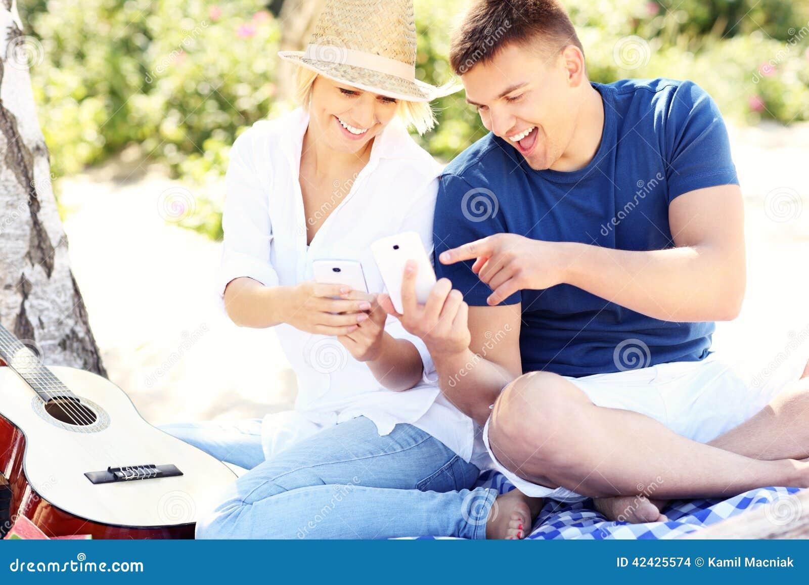 Pares jovenes usando smartphones en la playa