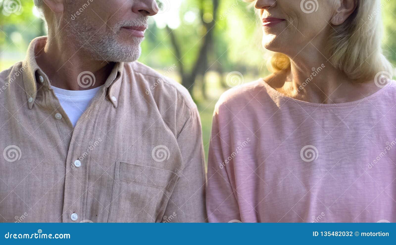 Pares jubilados que se miran, fecha romántica al aire libre, proximidad de la relación