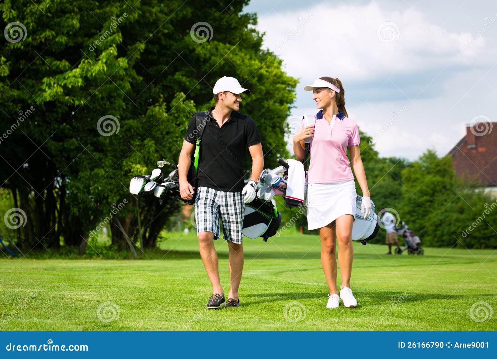 Pares juguetones jovenes que juegan a golf en un curso
