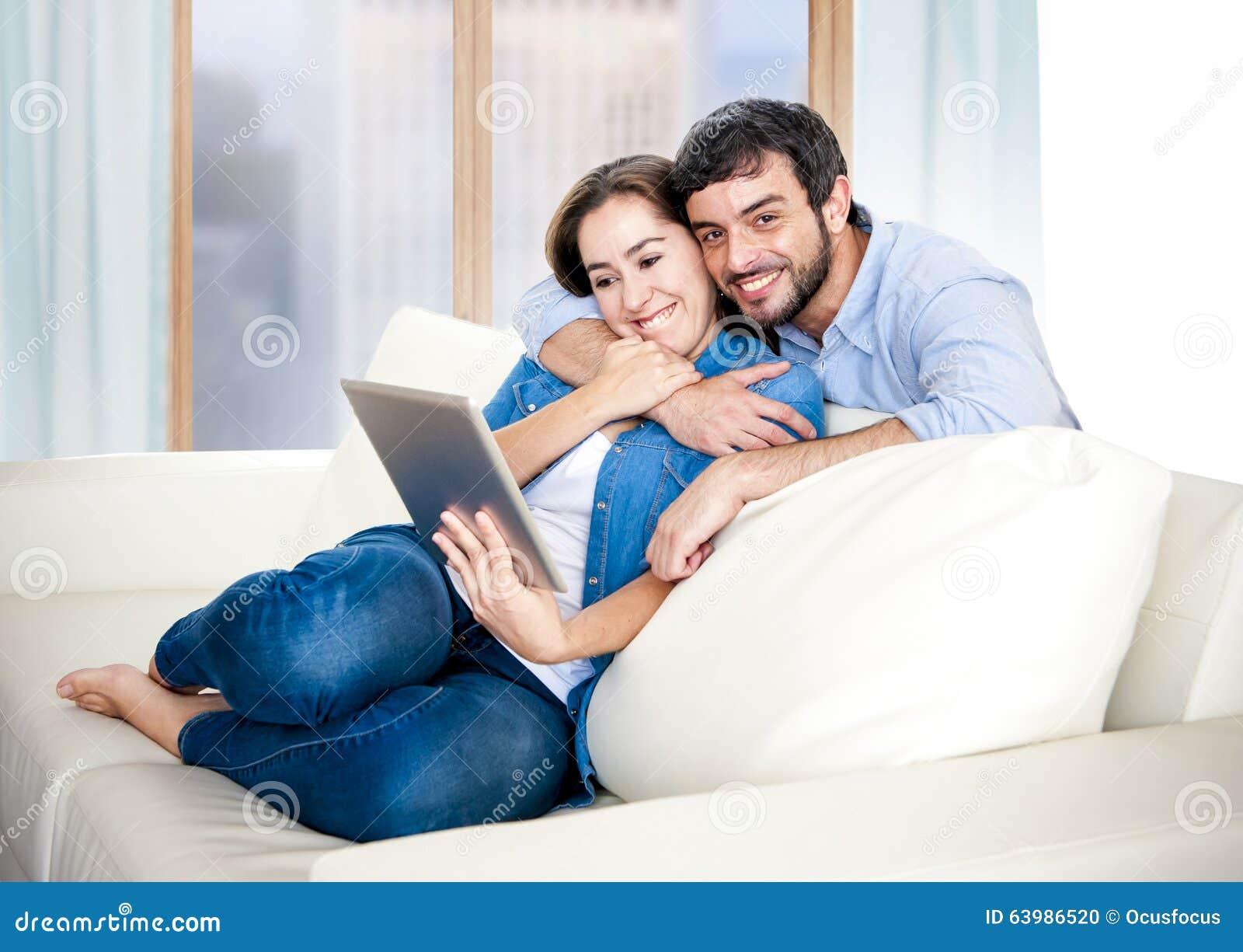 Pares latin bonitos no amor que encontra-se junto no sofá do sofá da sala de visitas que aprecia usando a tabuleta digital