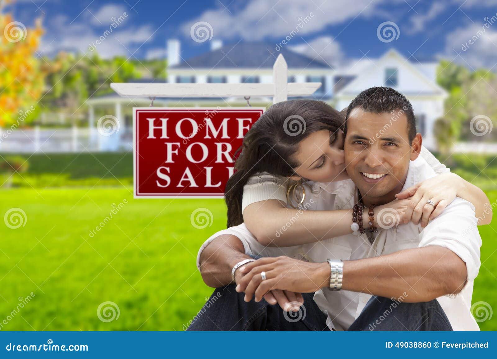 Pares latino-americanos afetuosos, casa nova e para o sinal de Real Estate da venda