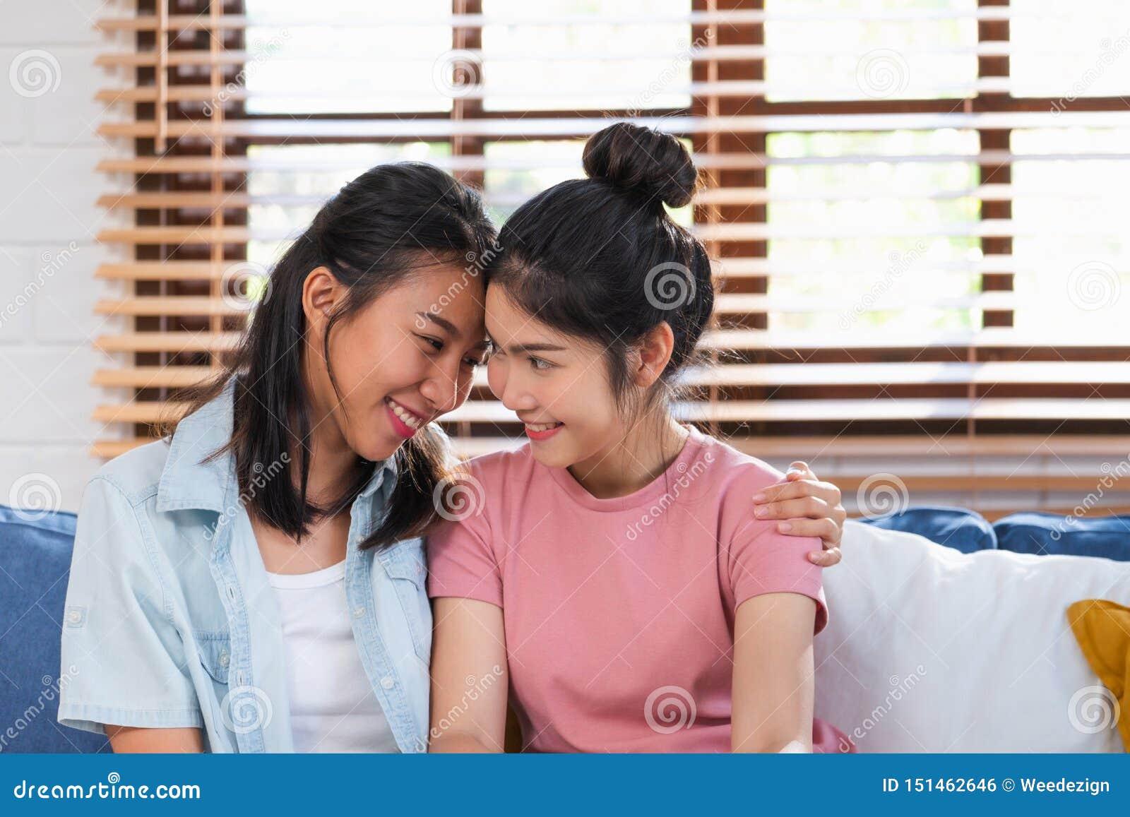 Pares lesbianos asiáticos felices abrazarse con amor en el sofá en la sala de estar en casa, concepto de la forma de vida de LGBT