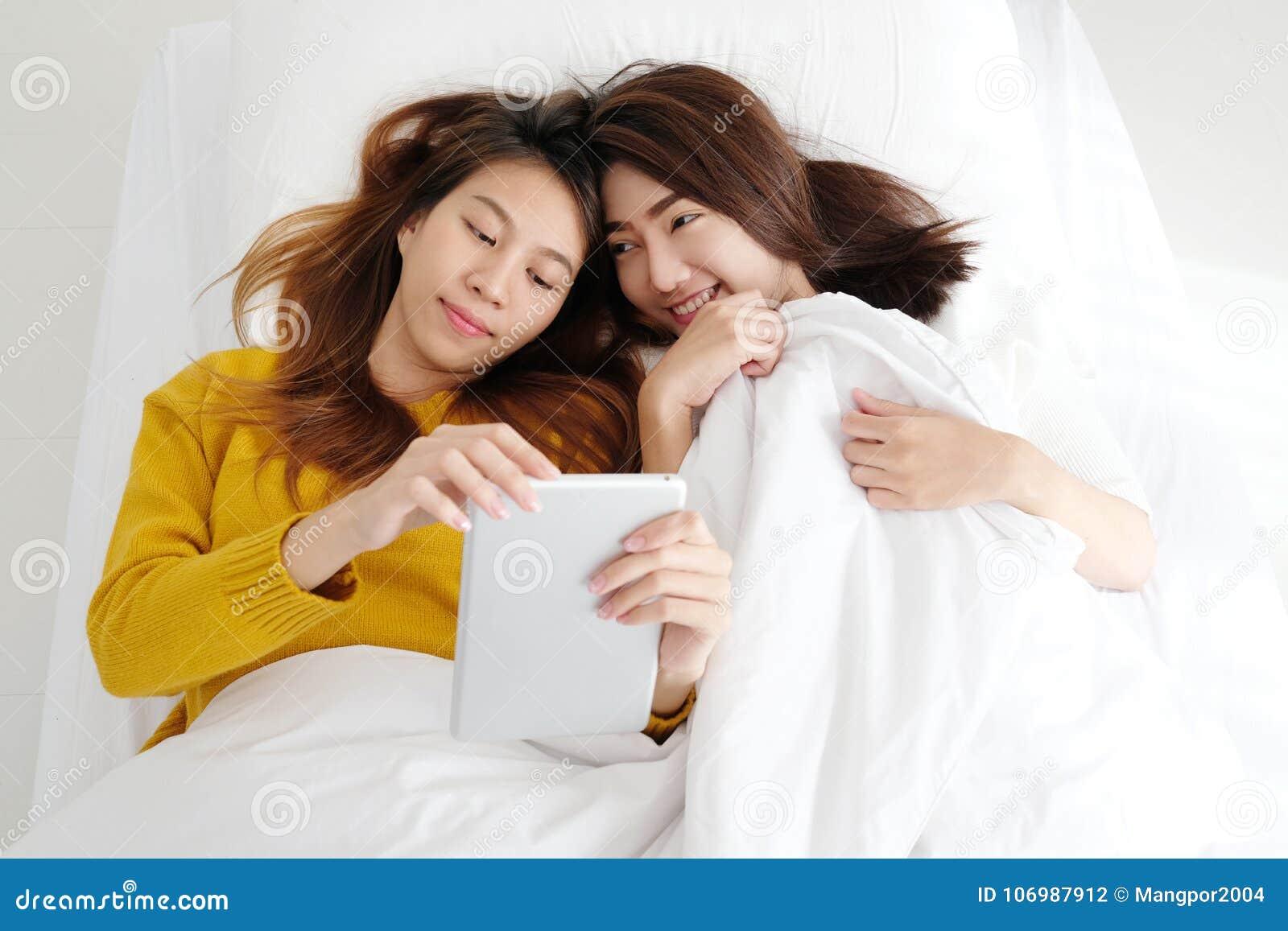 Pares lesbianos lindos jovenes de Asia usando la tableta con felicidad en wh