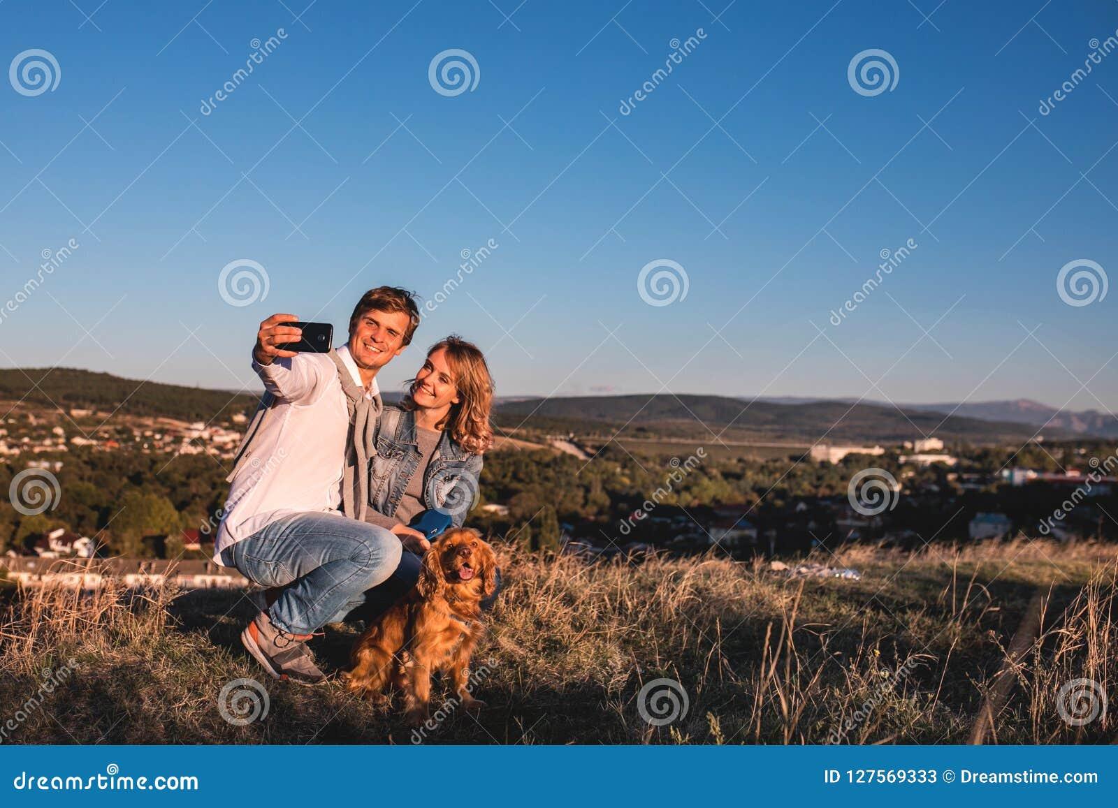 Pares lindos jovenes felices que hacen el selfie al aire libre