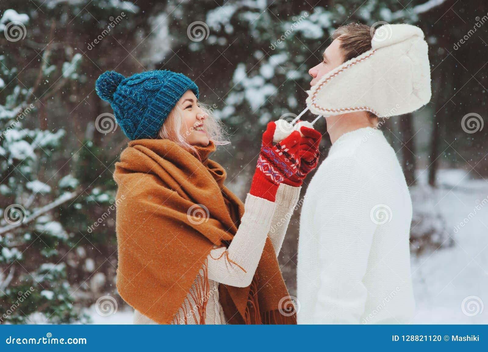 Pares loving novos felizes que andam na floresta nevado do inverno, coberta com a neve e o abraço