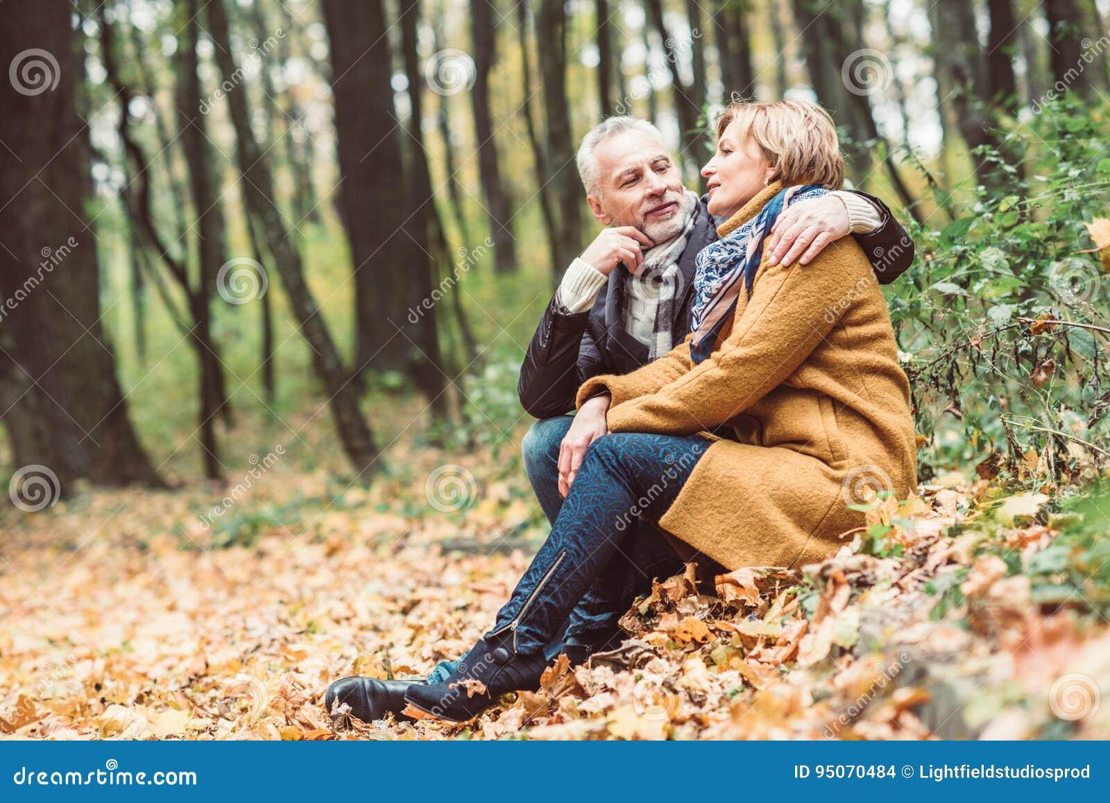 Pares maduros bonitos no parque do outono