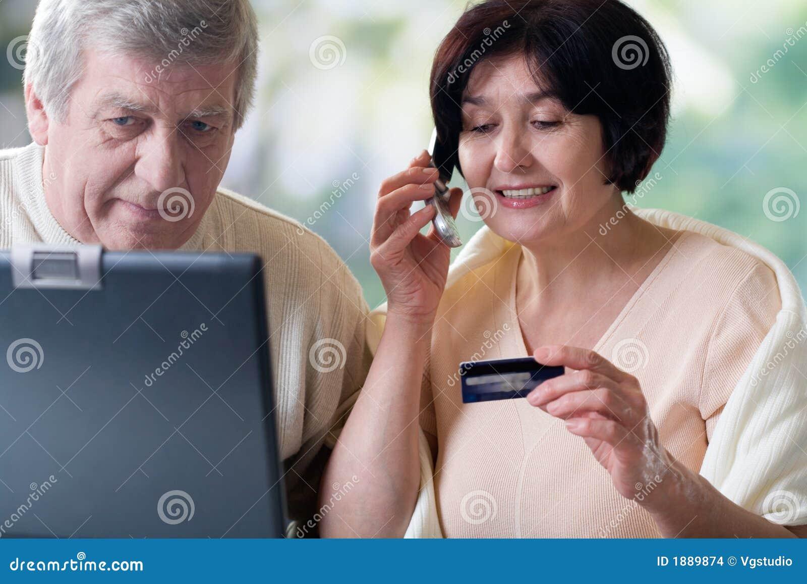 Pares maduros felices en la computadora portátil, haciendo compras en departamento del Internet