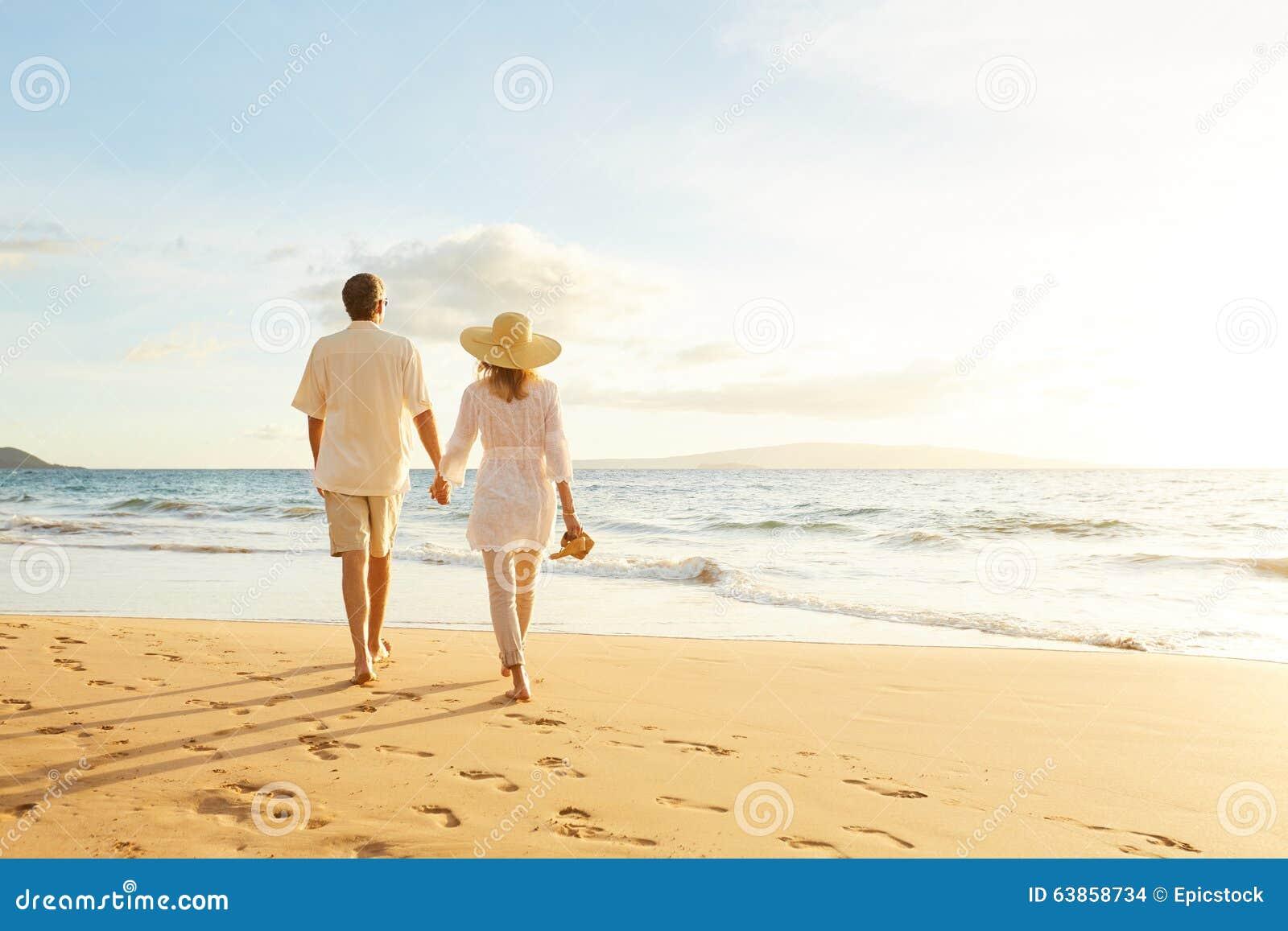 Pares maduros que andam na praia no por do sol