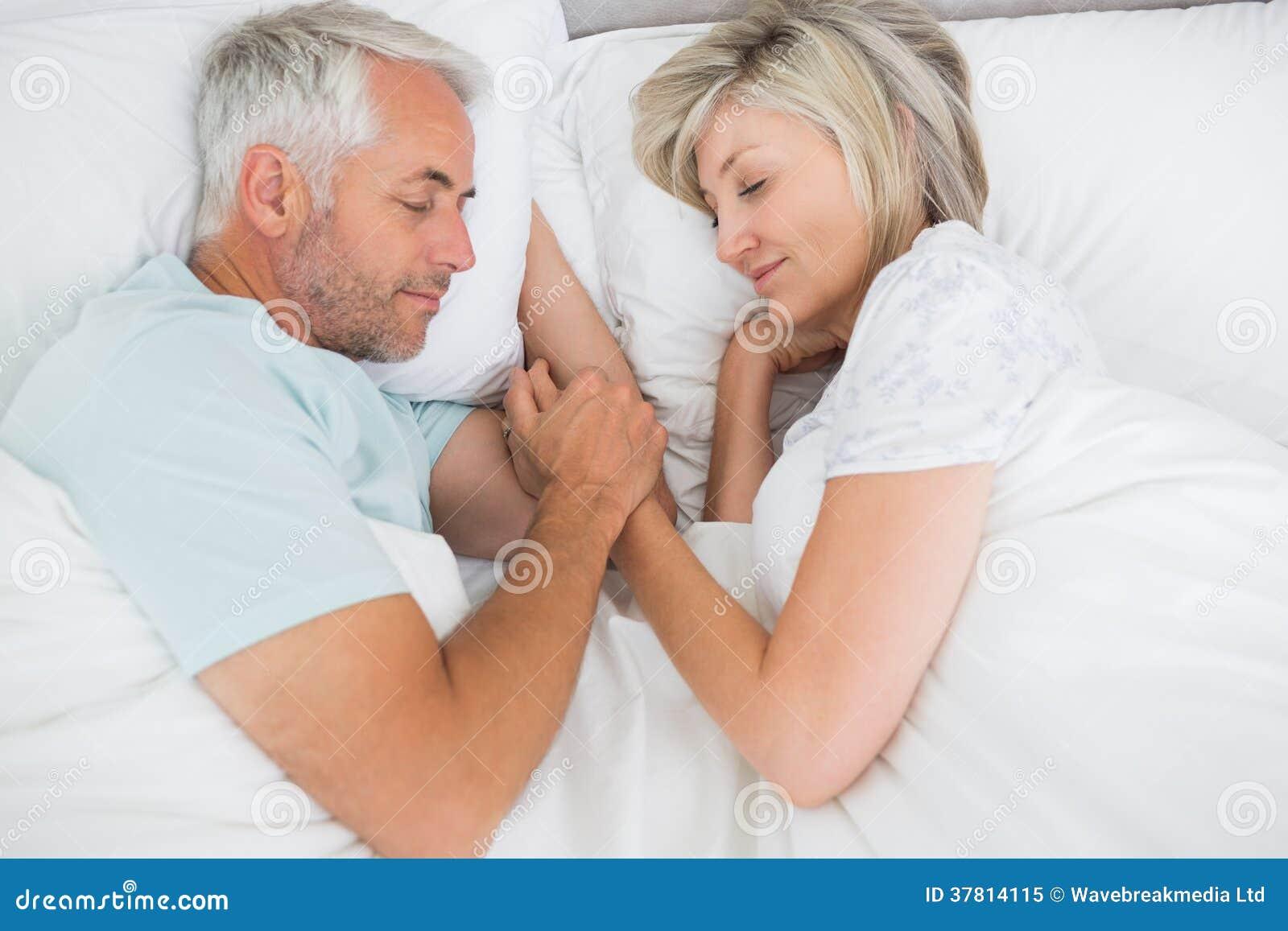 Pares maduros que encontram-se na cama em casa