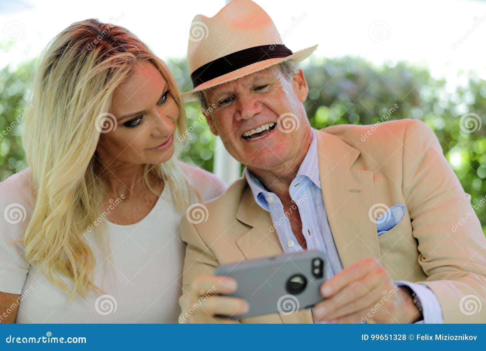 Pares maduros que olham fotos em um telefone celular e em um sorriso espertos