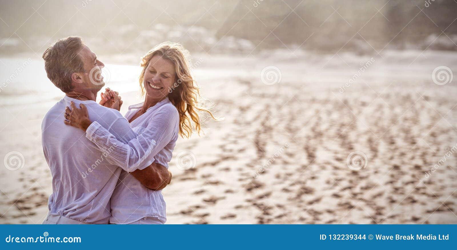 Pares maduros que se divierten junto en la playa