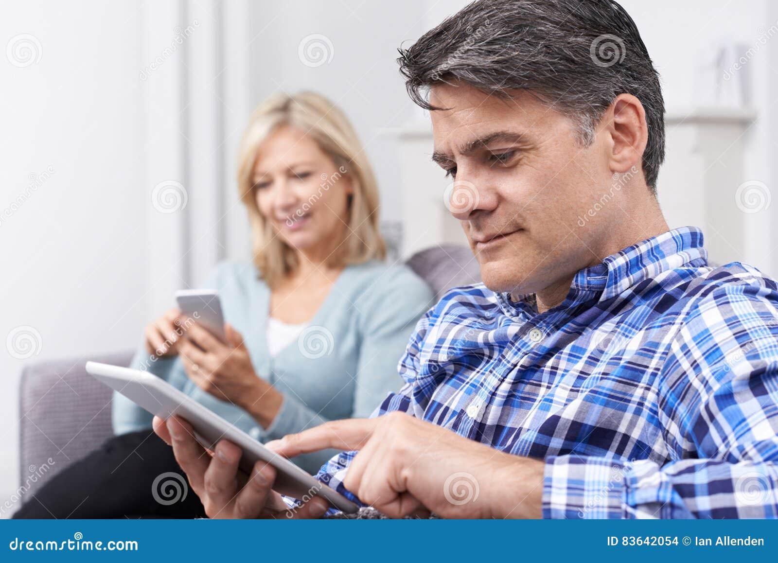 Pares maduros usando dispositivos de Digitas em casa