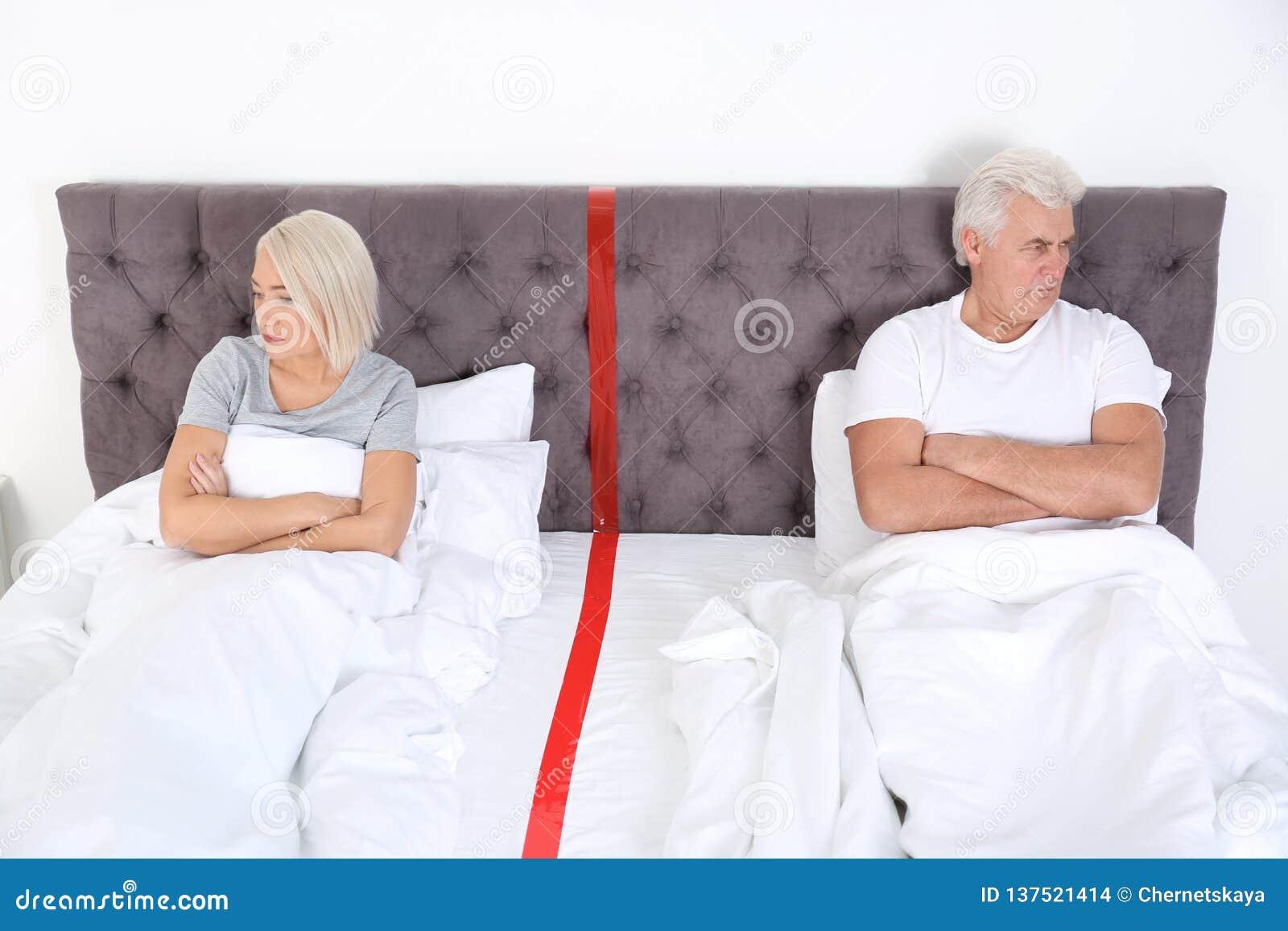 Pares maduros virados com os problemas do relacionamento que encontram-se separadamente na cama