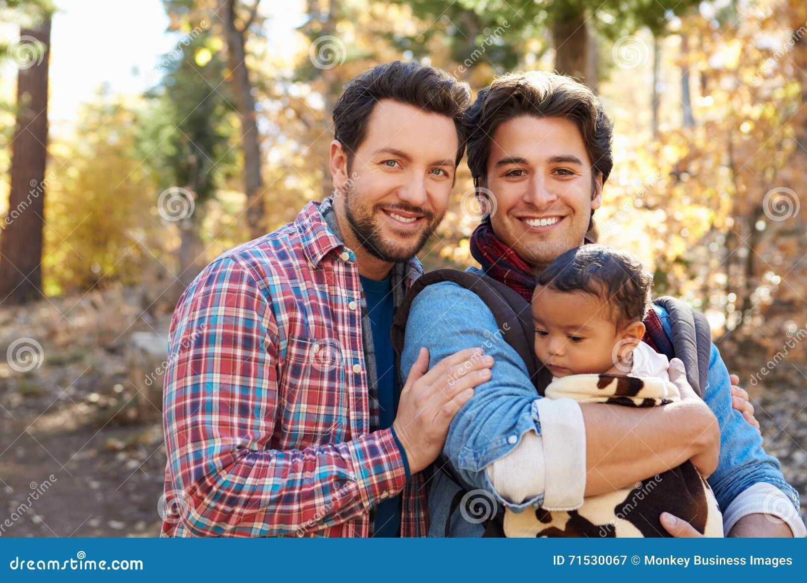 Pares masculinos alegres com o bebê que anda através da floresta da queda