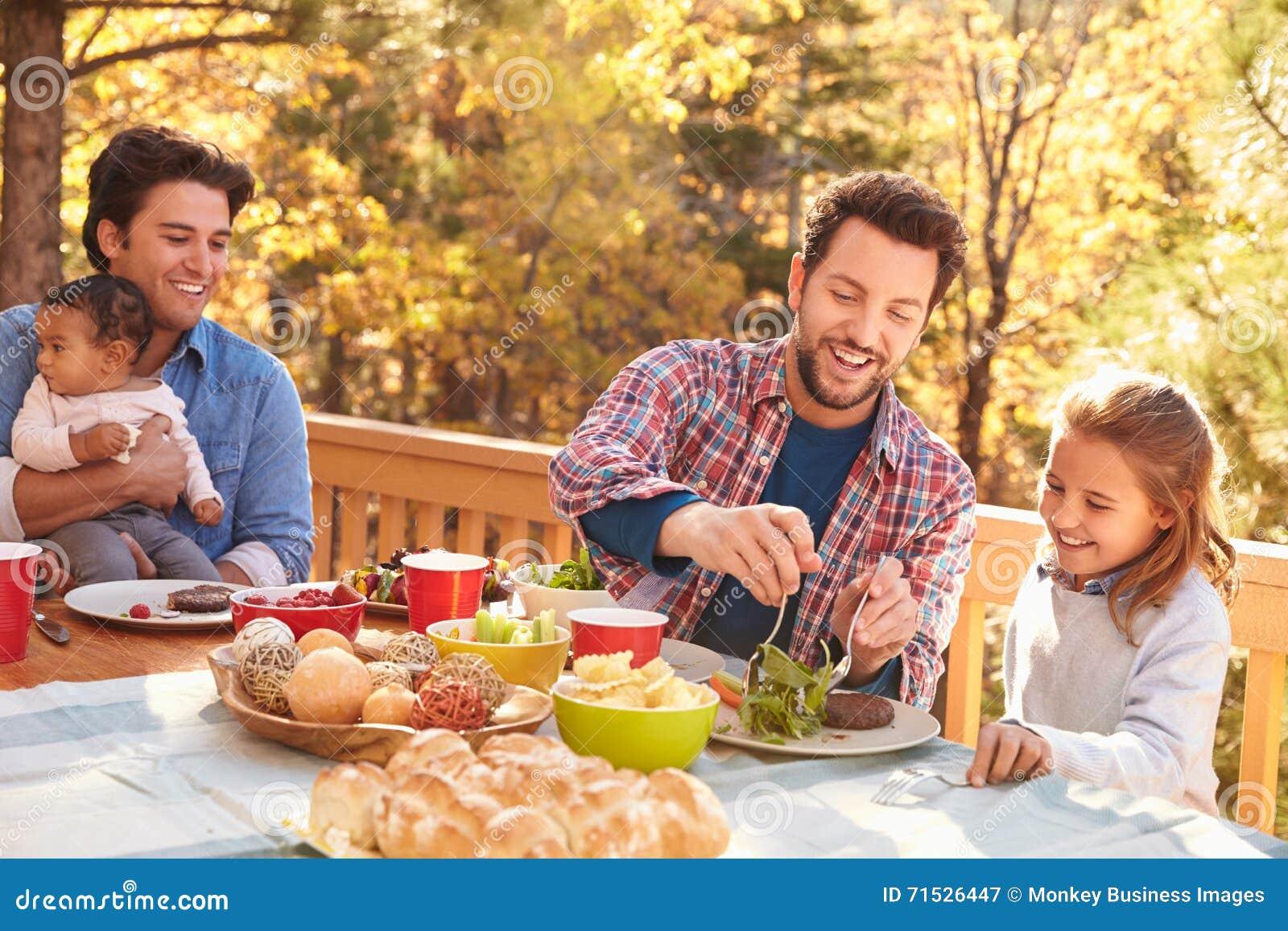Pares masculinos alegres que têm o almoço exterior com filhas