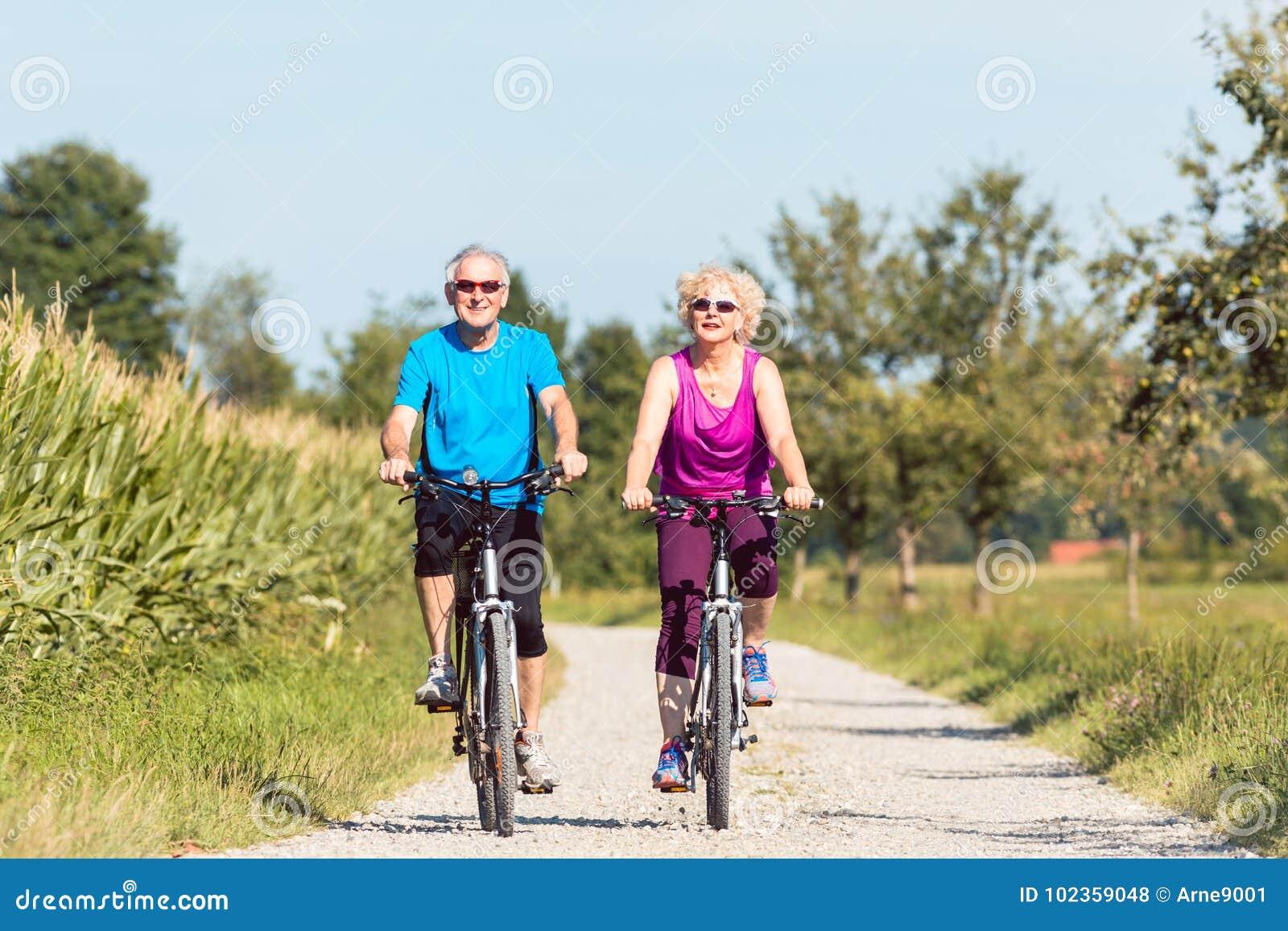 Pares mayores activos que disfrutan del retiro mientras que el montar monta en bicicleta i