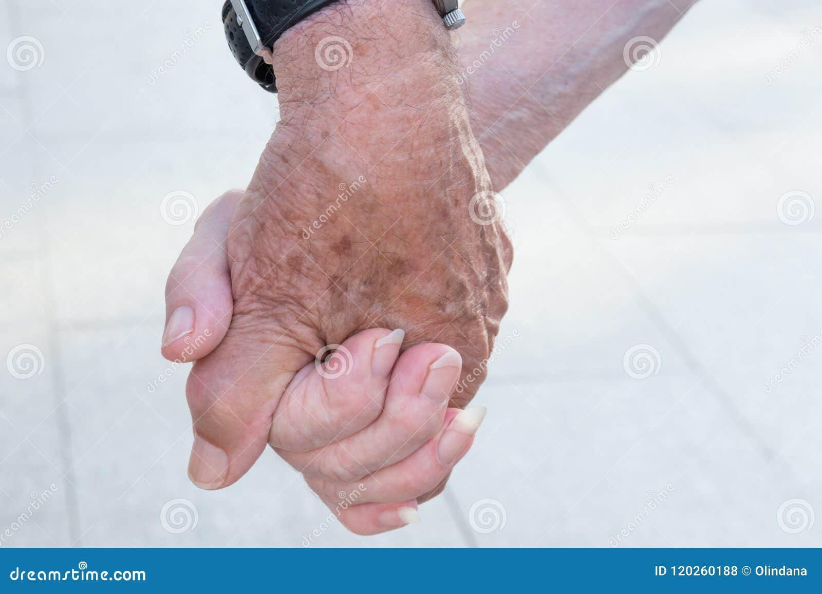 Pares mayores de la gente mayor que llevan a cabo las manos que caminan en la calle Unidad romántica Fidelity de la dedicación de