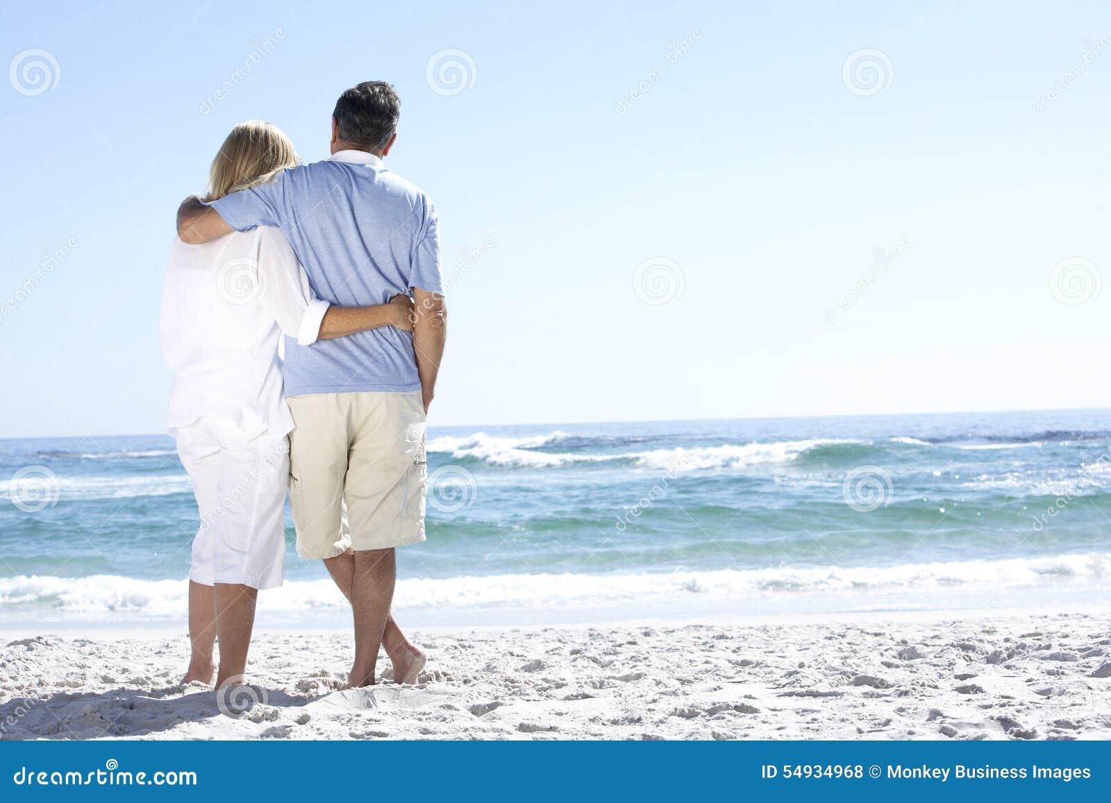 Pares mayores el día de fiesta que camina a lo largo del mar de Sandy Beach Looking Out To