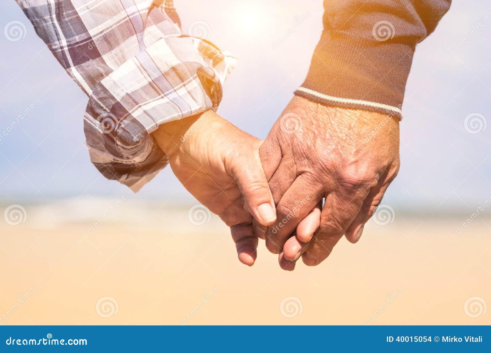 Pares mayores en el amor que camina en la playa que lleva a cabo las manos