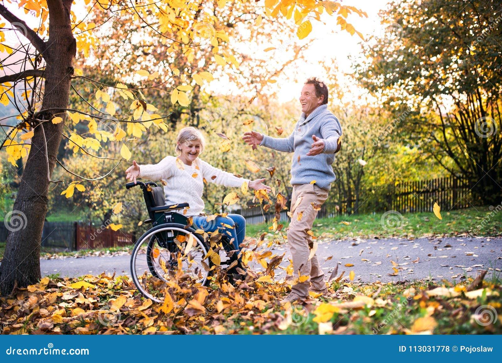 Pares mayores en silla de ruedas en naturaleza del otoño