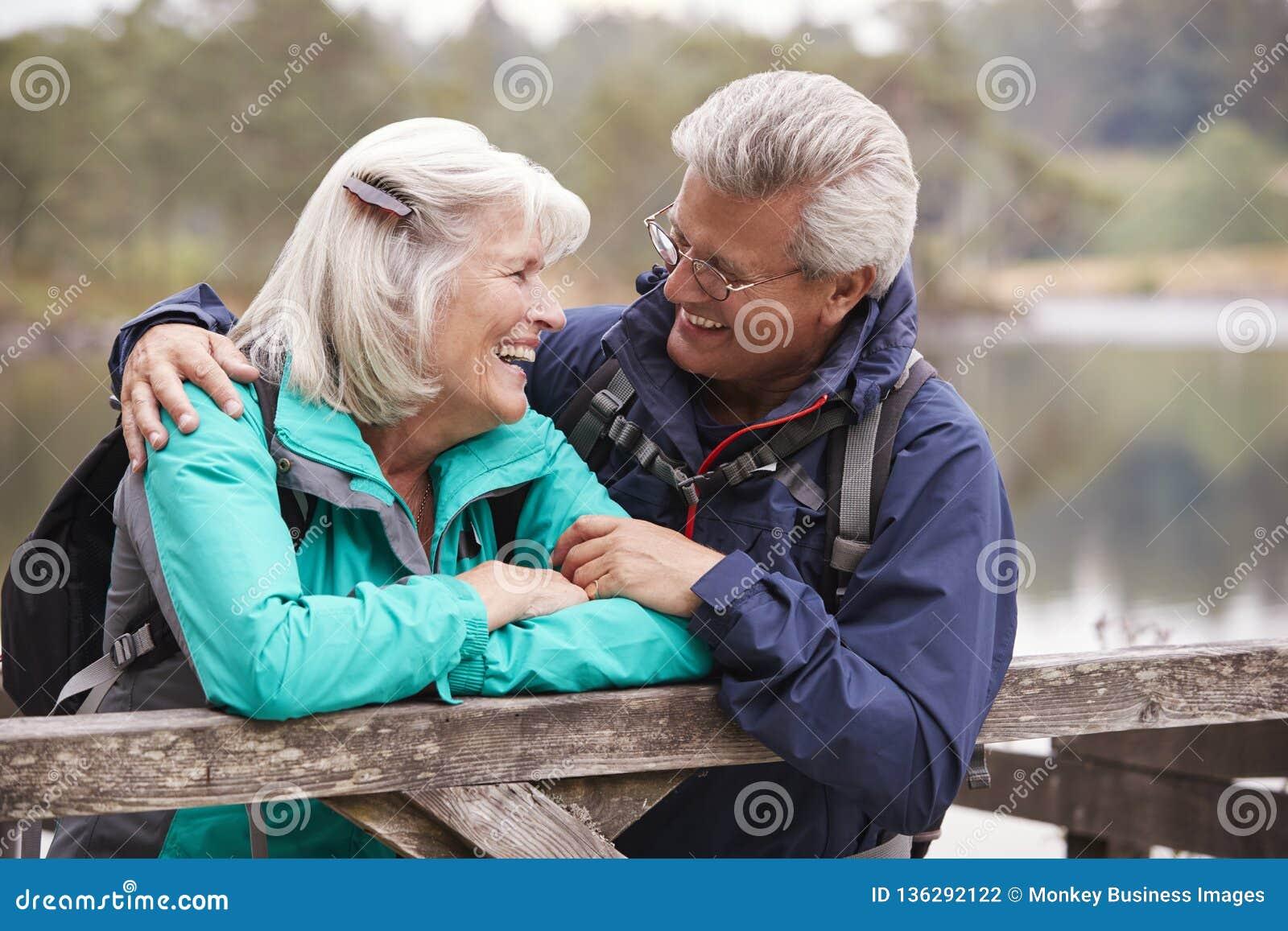 Pares mayores felices que se inclinan en una cerca de madera que sonríe el uno al otro, cierre para arriba, distrito del lago, Re