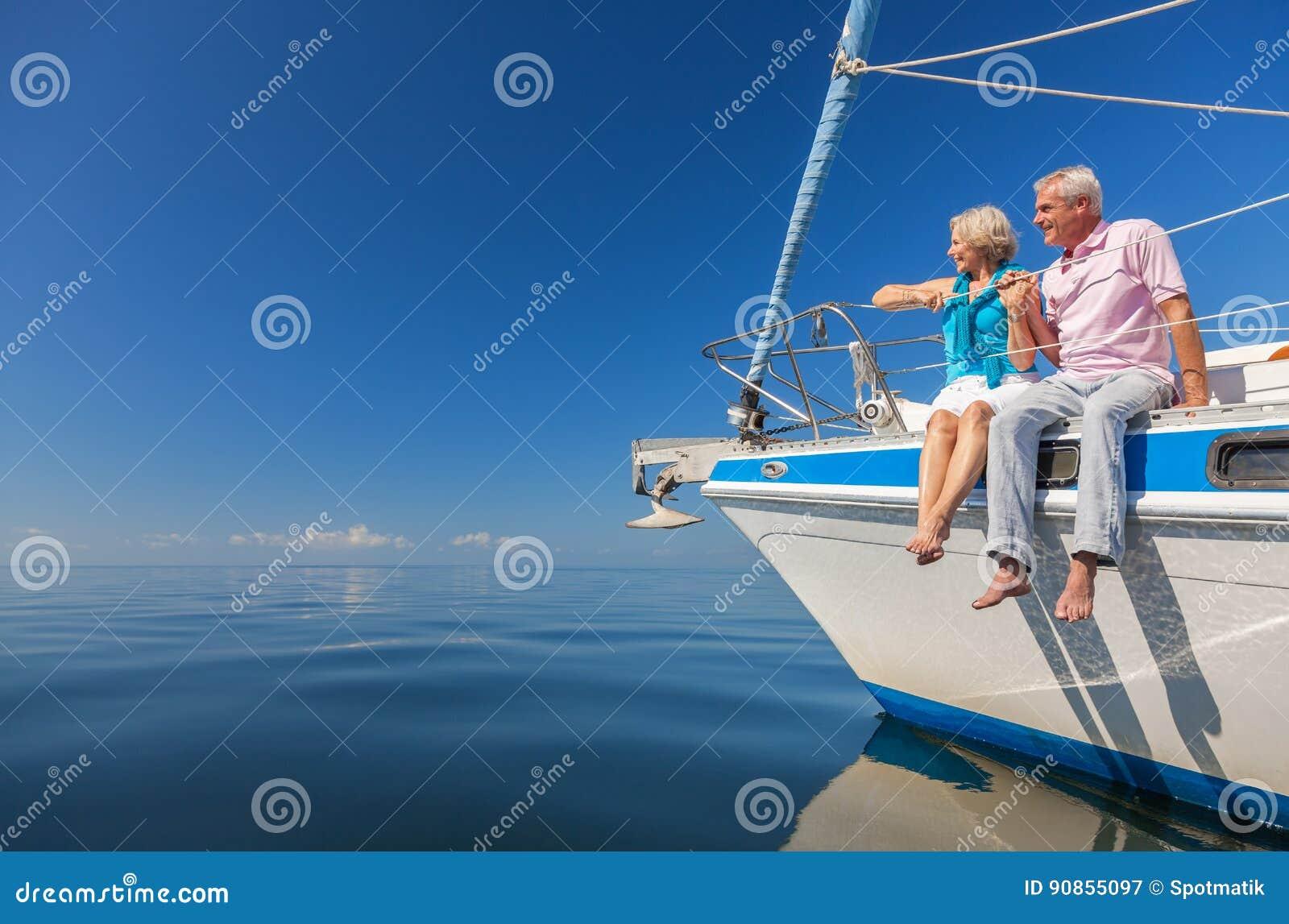 Pares mayores felices que se sientan en el lado de un barco de vela