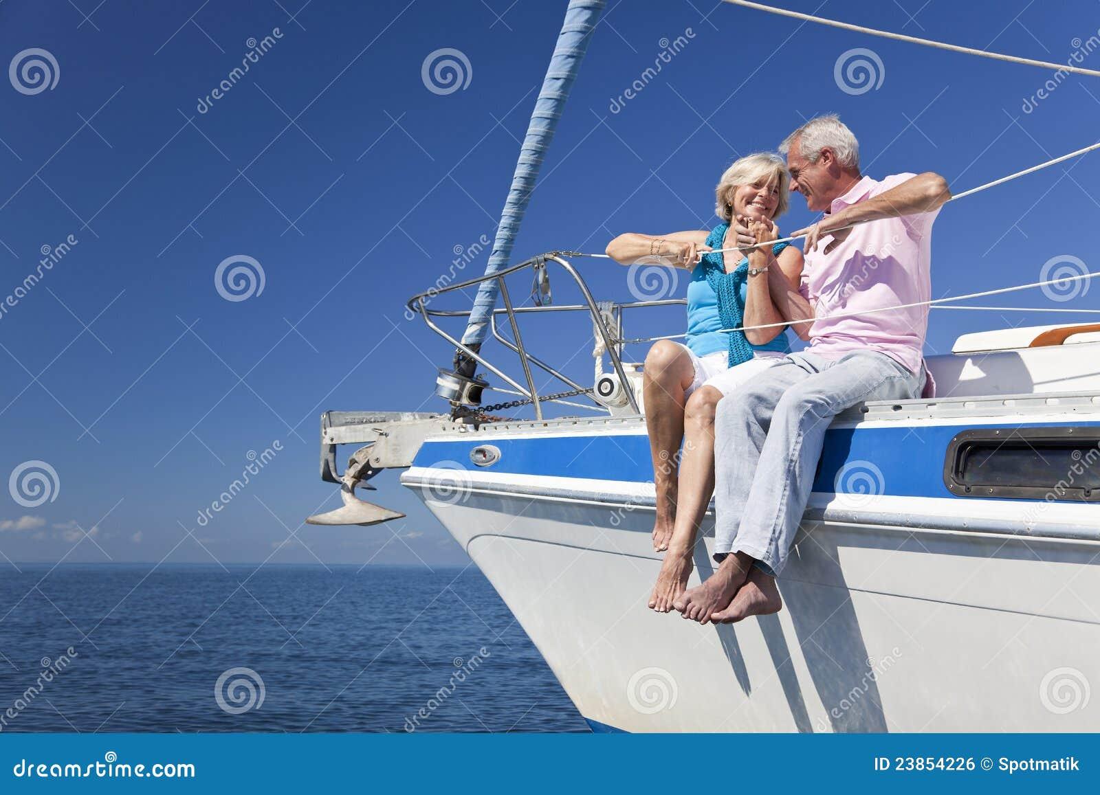 Pares mayores felices que se sientan en un barco de vela