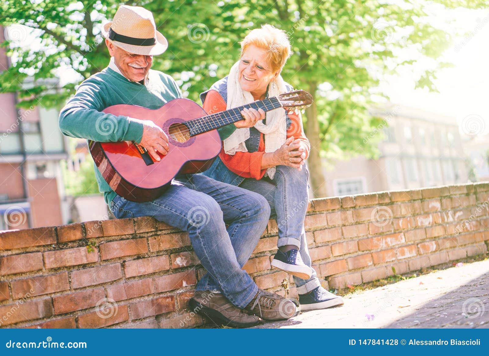 Pares mayores felices que tocan una guitarra mientras que se sienta afuera en una pared en un día soleado