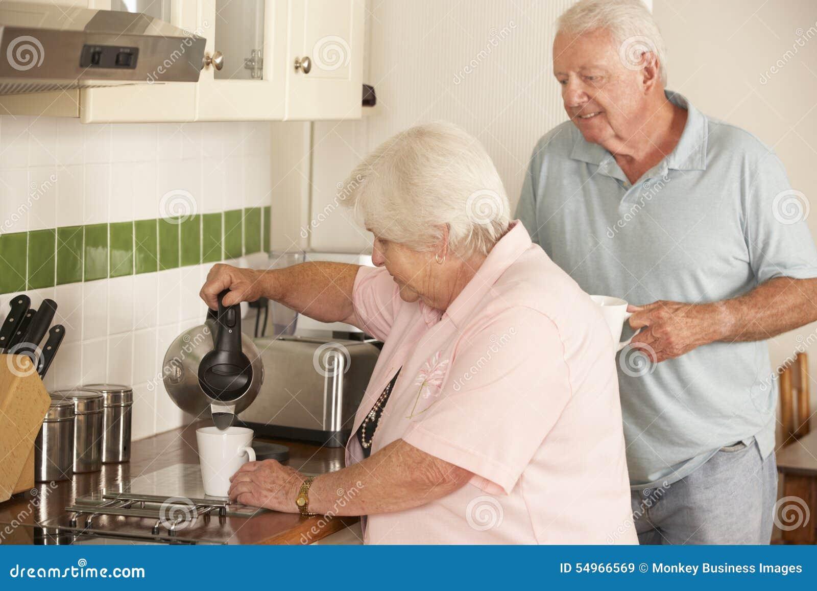 Pares mayores jubilados en la cocina que hace la bebida caliente junto