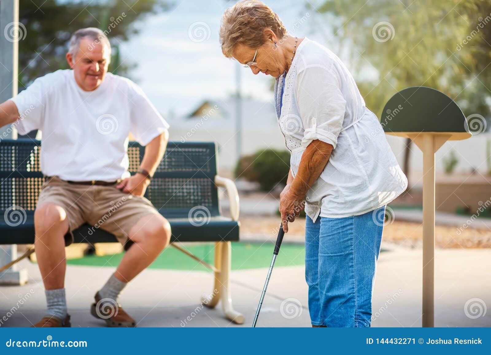 Pares mayores jubilados que juegan al mini golf junto