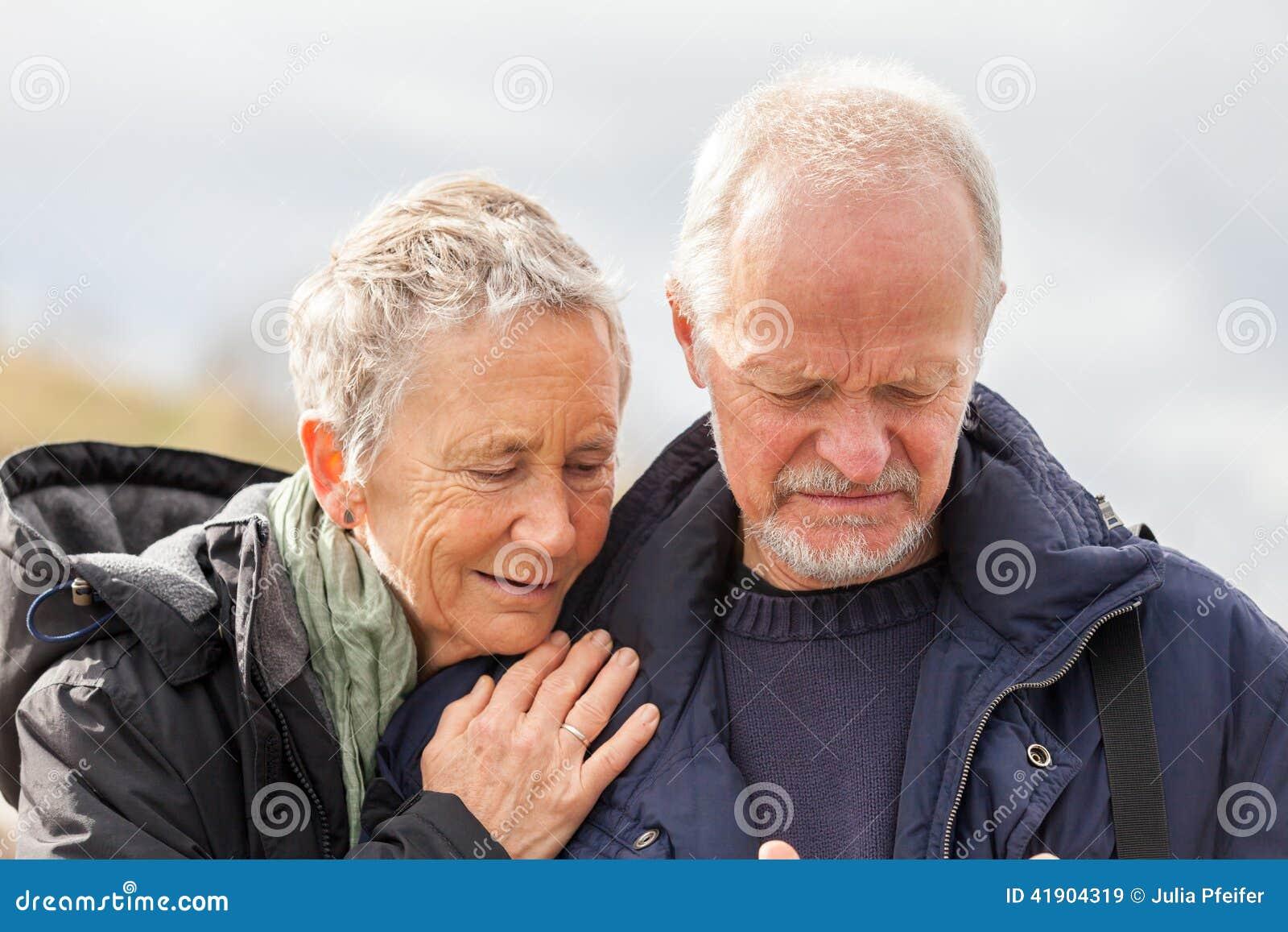 Pares mayores mayores felices que caminan en la playa