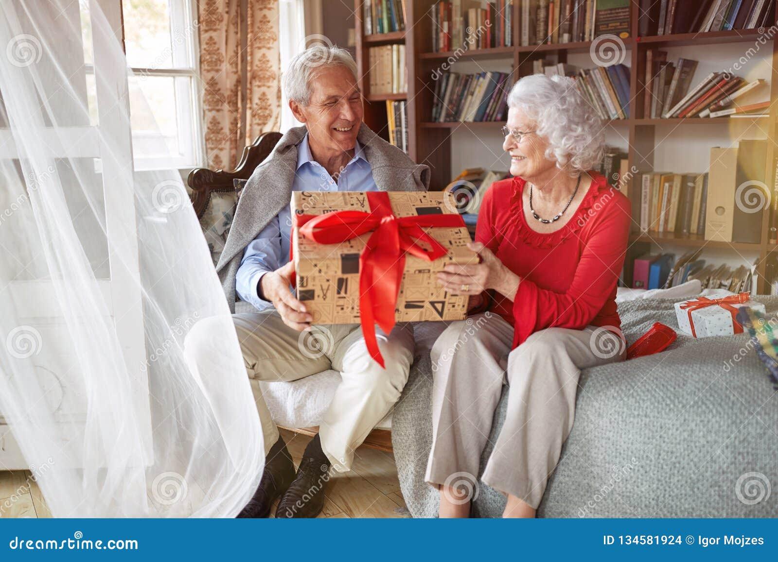 Pares mayores preciosos que intercambian los regalos de la Navidad