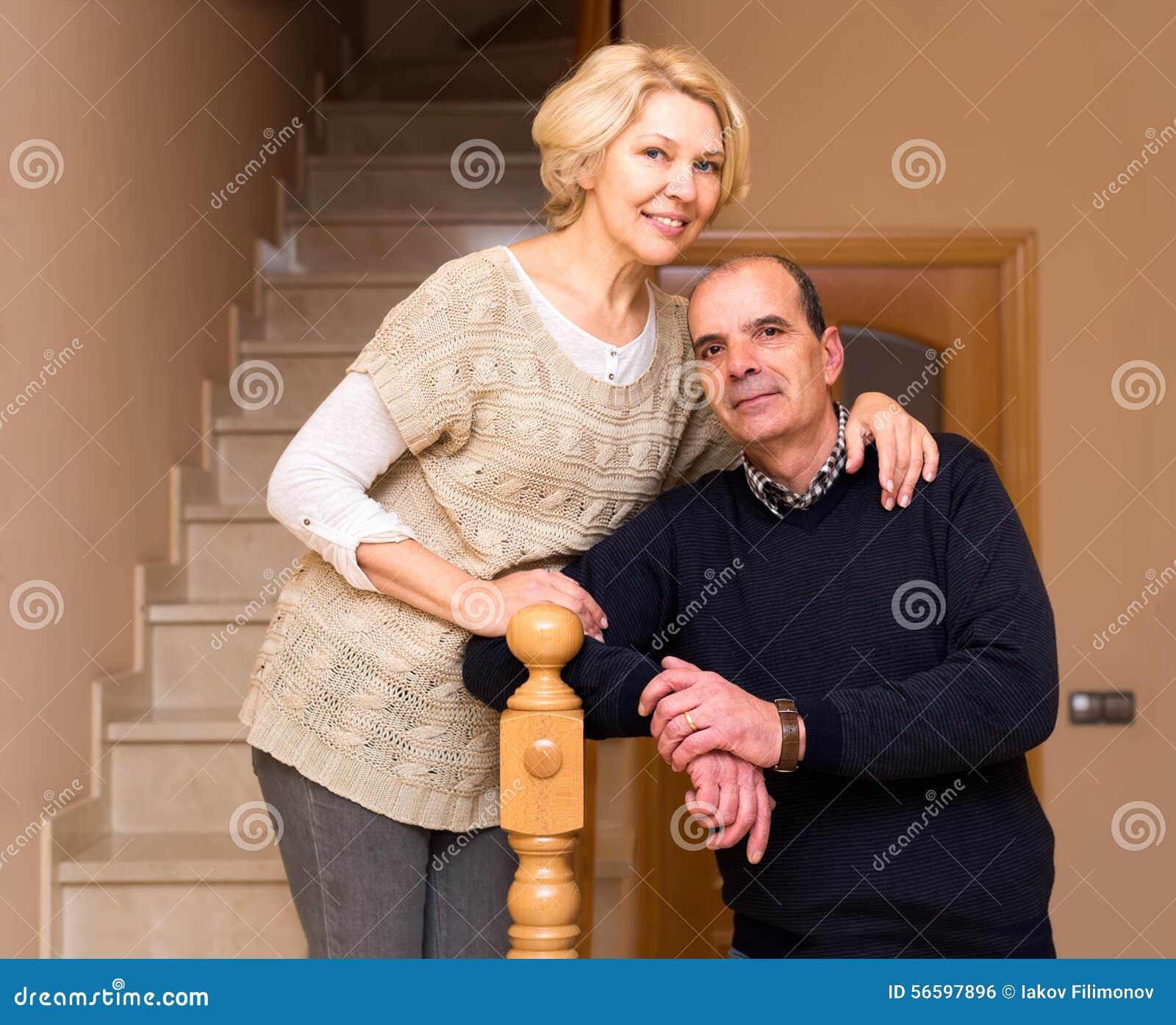 Pares mayores que abrazan en las escaleras
