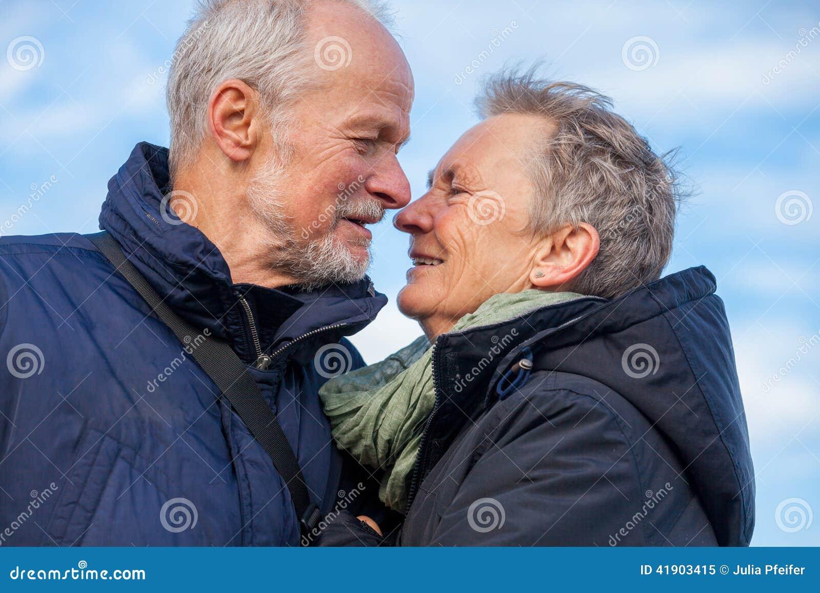 Pares mayores que abrazan y que celebran el sol