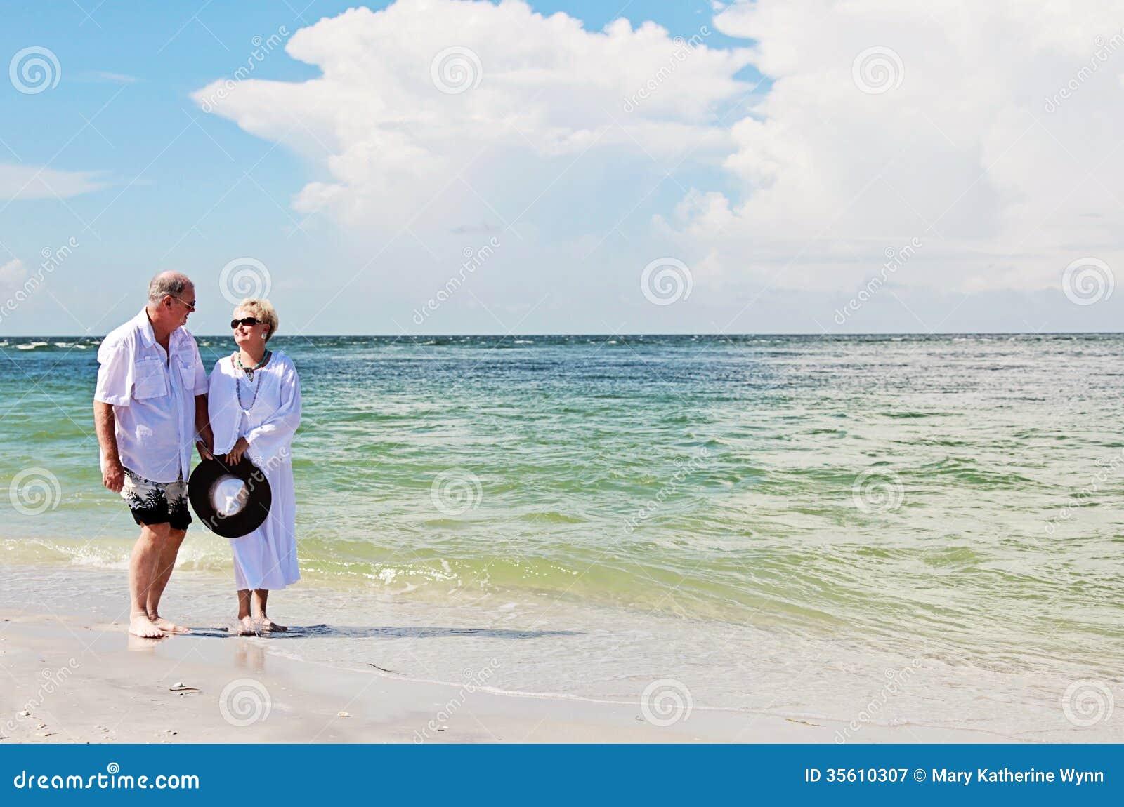 Pares mayores que caminan en la playa