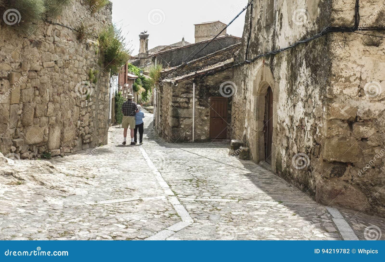 Pares mayores que caminan en una calle medieval en Trujillo, España