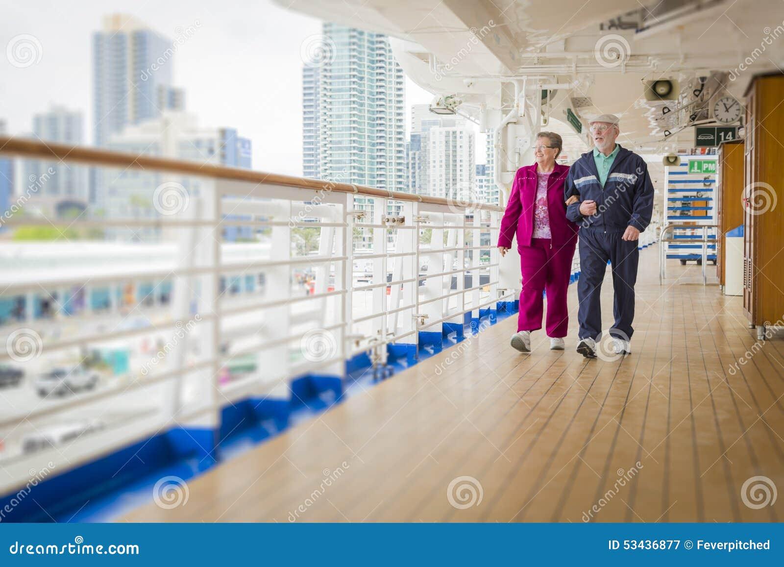 Pares mayores que gozan de la cubierta de un barco de cruceros