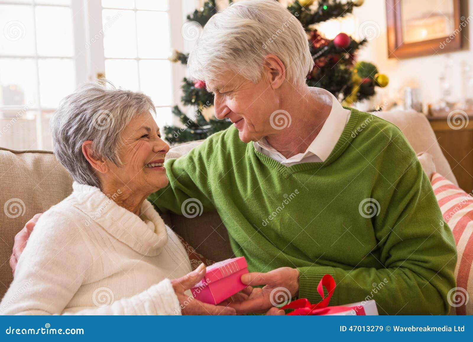 Pares mayores que intercambian los regalos de la Navidad