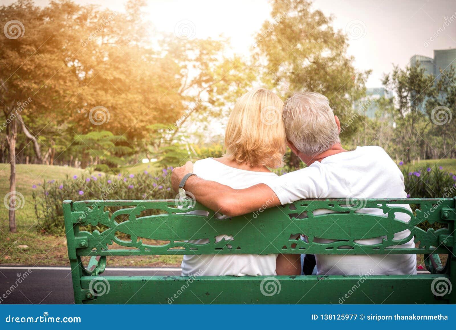 Pares mayores que localizan en un banco y que tienen tiempo romántico y relajante en un parque