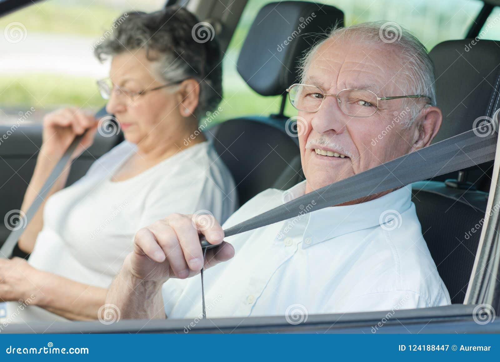 Pares mayores que ponen en sus cinturones de seguridad