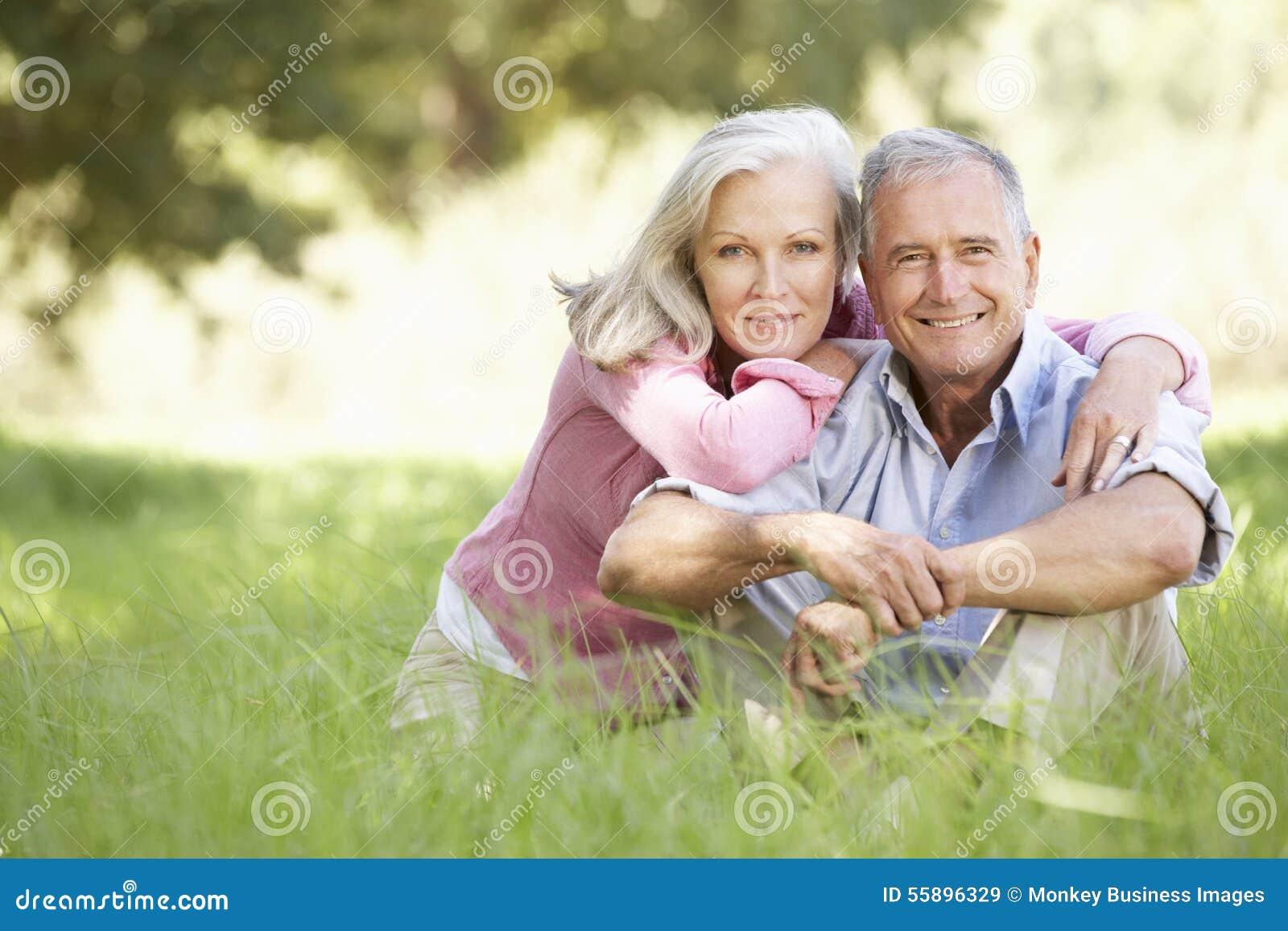 Pares mayores que se relajan en Sunny Summer Field