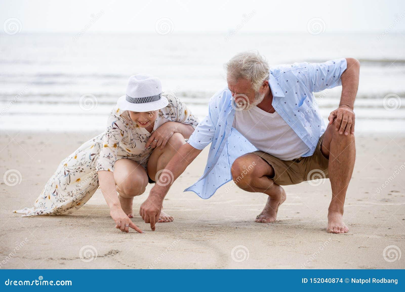 Pares mayores que se sientan en la playa que dibuja un corazón en la arena junto, caucásico asiático del hombre de la mujer
