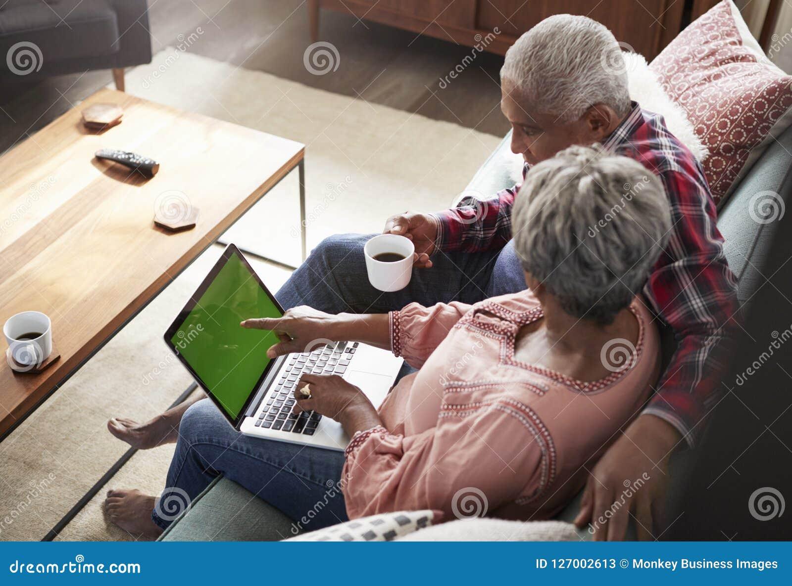 Pares mayores que se sientan en Sofa At Home Using Laptop para hacer compras en línea